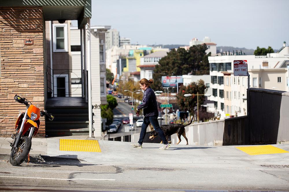 Een vrouw loopt met haar hond in San Francisco. De Amerikaanse stad San Francisco aan de westkust is een van de grootste steden in Amerika en kenmerkt zich door de steile heuvels in de stad.<br /> <br /> A woman is walking her dog at San Francisco. The US city of San Francisco on the west coast is one of the largest cities in America and is characterized by the steep hills in the city.