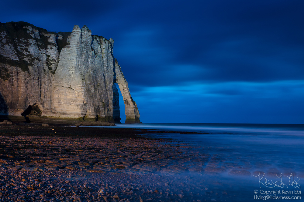 At dusk, English Channel waves crash through a natural sea arch known as Porte d'Aval at the Falaise d'Étretat cliffs in Normandy, France. The white chalk cliffs are as tall as 90 meters (300 feet).