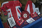 A window display of a high street funeral directors showing patriotic Union Jacks and replica medals of a local man, Second Lieutenant Reginald Cuthbert Chilvers of the Norfolk Regiment, a casualty in 1917 during WW1, on 7th November 2019, in Surbiton, London, England.