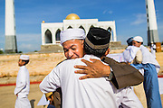 28 JULY 2014 - KHLONG HAE, SONGKHLA, THAILAND: Men greet each other after Eid services at Songkhla Central Mosque in Songkhla province of Thailand. Eid al-Fitr is also called Feast of Breaking the Fast, the Sugar Feast, Bayram (Bajram), the Sweet Festival and the Lesser Eid, is an important Muslim holiday that marks the end of Ramadan, the Islamic holy month of fasting.   PHOTO BY JACK KURTZ