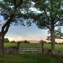 A stone wall, maple trees, and a gate mark a hay field at the Canterbury Shaker Village in Canterbury, New Hampshire.