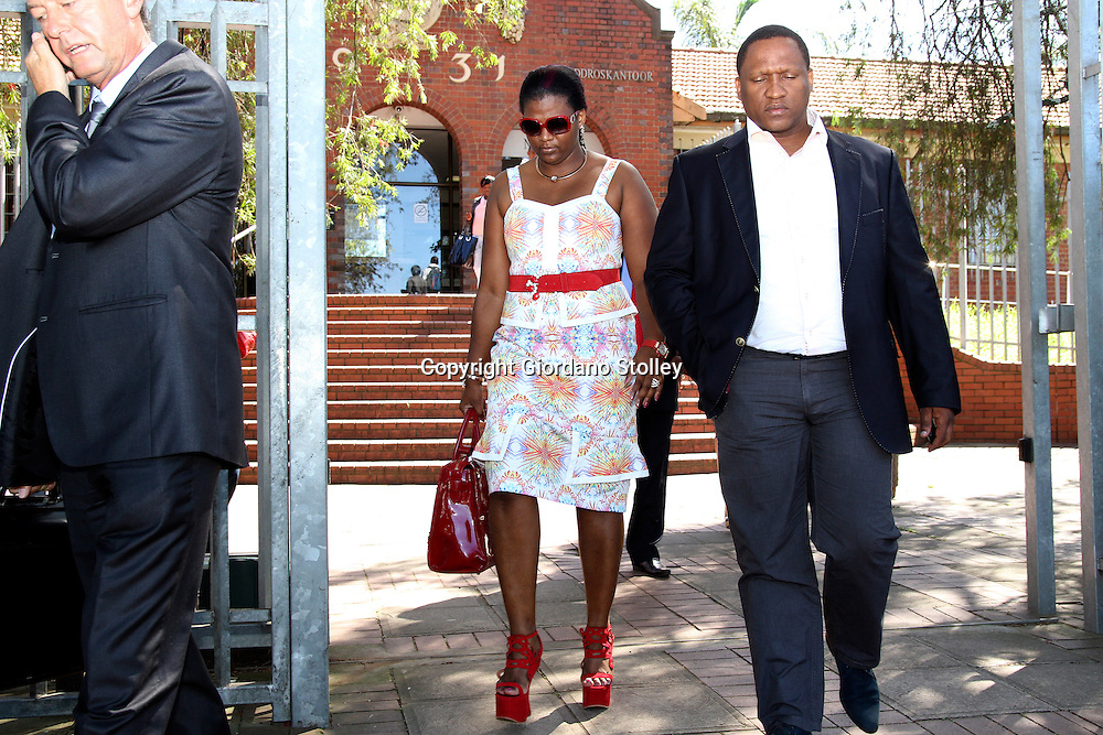 """DURBAN - 21 February 2013 - Durban business woman Mabongi Flora-Junior """"Shauwn"""" Mpisane (center) leaves the Pinetown Magistrates Court along with husband Sibusiso Mpisane Mpisane (right) after being told she will stand trial on charges of fraud, corruption and defeating the ends of justice in September. On the phone on the left is her lawyer JimmyHowse. Shauwn is accused of attempting to get a state witness to alter invoices that are evidence in another case involving tax evasion. Picture: Giordano Stolley/Allied Picture Press/APP"""