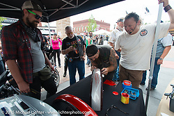 Harley-Davidson's Vehicle Collections and Restorer Specialist Bill Rodencal at a pin striping demo at the new Harley-Davidson Rally Point on Harley Way and Main Street during the 75th Annual Sturgis Black Hills Motorcycle Rally.  SD, USA.  August 4, 2015.  Photography ©2015 Michael Lichter.