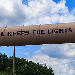 """Mahanoy City, PA - June 22, 2016:  A conveyor used to move coal over a road with the words """"Coal Keeps the Lights On"""" painted on it."""