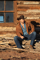 cowboy sitting on a pile of wood by a rustic cabin