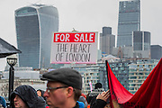 A rally at the end at the foot of City Hall and sandwiched between the City and a new development of luxury flats at One Tower Bridge. People marched from South London and East London to City Hall to demand better homes for Londoners and an end to the housing crisis. Demands included rent controls, affordable and secure homes for all, an end to the Bedroom Tax and welfare caps and the building of new council houses. The event was called by Defend Council Housing and  South London People's Assembly. And the East London route started at Parish Church of St. Leonard, Shoreditch, London, United Kingdom. 31 Jan 2015.Guy Bell, 07771 786236, guy@gbphotos.com