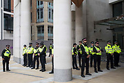 City of London Police line up outside the London Stock Exchange in Paternoster Square during an Extinction Rebellion Blood Money March through the City of London on 27th August 2021 in London, United Kingdom. Extinction Rebellion were highlighting financial institutions funding fossil fuel projects, especially in the Global South, as well as law firms and institutions which facilitate them.