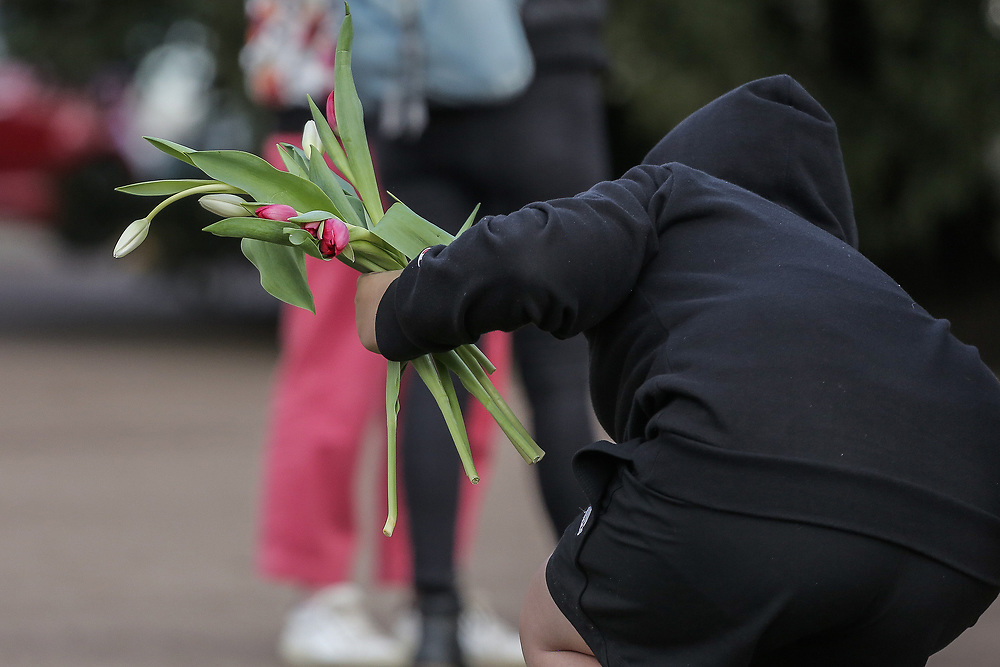 13th, March, 2021. Cheltenham, England.<br /> A member of the public handling flowers ready for laying in memory of Sarah Everard.