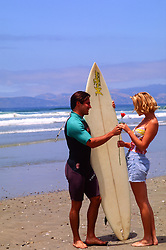 surfer giving a rose to a beautiful girl on the beach