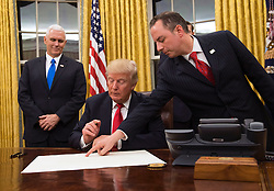 President Donald Trump prepares to sign a confirmation for Defense Secretary James Mattis as his Chief of Staff Reince Priebus points to the order while Vice President Mike Pence watches, at the White House in Washington, D.C. on January 20, 2017. Photo by Kevin Dietsch/UPI