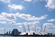 The O2 Arena (formerly the Millennium Dome) is seen in sunshine on the Greenwich Peninsula, beneath a blue sky and clouds, on 11th August 2021, in London, England. The O2 is a music, sport and entertainment venue, opened in the year 2000.