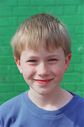 Portrait of young boy standing outside smiling,