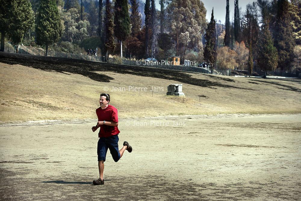Griekenland.Peloponnesos.Olympia.29 augustus 2007..Toerist rent over de atlethiekbaan van het oude Olympia.