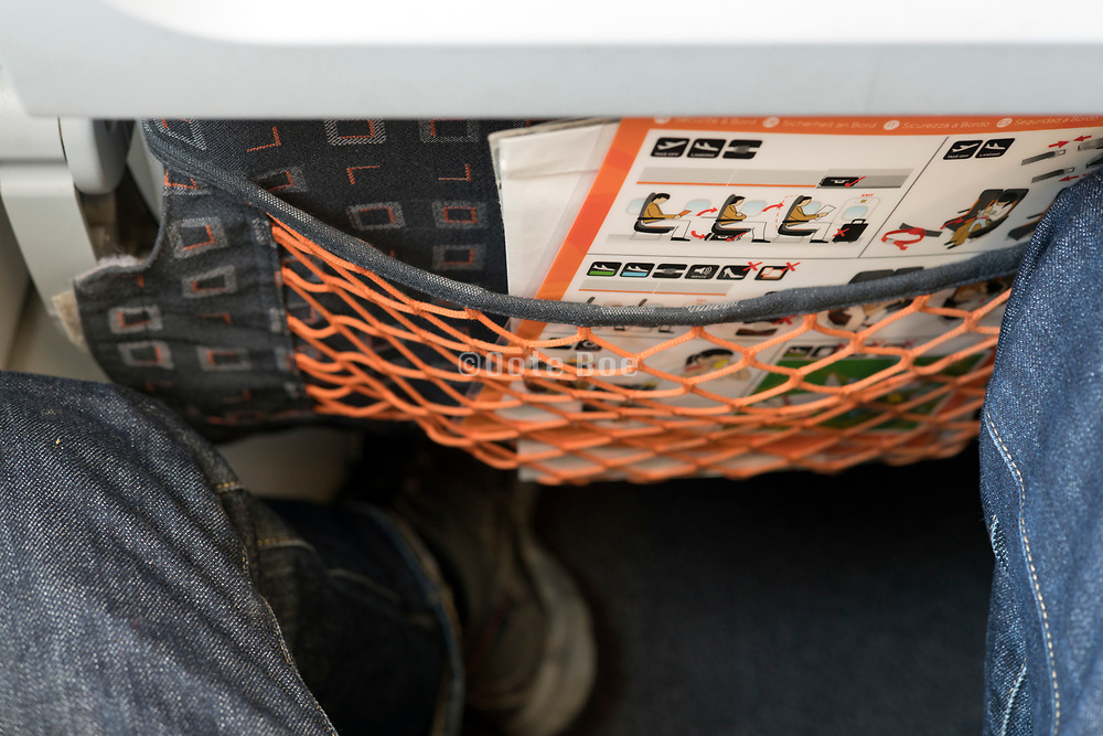 legroom in airplane with safety notice in the front seat