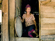 A Laoseng minority woman in the doorway of her home in the remote and roadless village of Ban Phouxoum, Phongsaly province, Lao PDR. Ban Phouxoum is situated along the Nam Ou river (a tributary of the Mekong) and has been temporarily relocated due to the construction of the Nam Ou Cascade Hydropower Project Dam 6. The Nam Ou river connects small riverside villages and provides the rural population with food for fishing. But this river and others like it, that are the lifeline of rural communities and local economies are being blocked, diverted and decimated by dams. The Lao government hopes to transform the country into 'the battery of Southeast Asia' by exporting the power to Thailand and Vietnam.