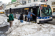 Some people wrapped up in warm clothes, carefully walk over snow mounds to board the M14D bus on 728 Amsterdam Avenue, New York City,  New York, United States of America, after the snowstorm in January 2016. The snowstorm brought more than 2 feet of snow in many areas, which broke many records.