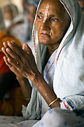 Widows chant in an ashram for a meagre allowance of money. Abandoned by their famiies they are dumped in  the holy city of Vrindavan, India