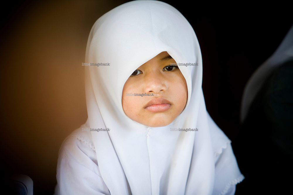 A small girl wearing a veil in a gathering in Southern Thailand. Thailand is struggling to keep up appearances as the land of smiles has to face up to its troubled south. Since 2004 more than 3500 people have been killed and 4000 wounded in a war we never hear about. In the early hours of January 4th 2004 more than 50 armed men stormed a army weapons depot in Narathiwat taking assault rifles, machine guns, rocket launchers, pistols, rocket-propelled grenades and other ammunition. Arsonists simultaneously attacked 20 schools and three police posts elsewhere in Narathiwat. The raid marked the start of the deadliest period of armed conflict in the century-long insurgency. Despite some 30,000 Thai troops being deployed in the region, the shootings, grenade attacks and car bombings happen almost daily, with 90 per cent of those killed being civilians. 19.09.2009. Photo: Christopher Olssøn