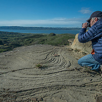 A photographer shoots  eroded rock features overlooking Fort Peck Reservoir in Charles M. Russell National Wildlife Reserve, Montana.