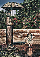 Drops of water falling from the Rain Man statue's umbrella fascinate a little boy.  Aspect Ratio 1w x 1.4h.