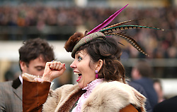 A female racegoer reacts watching the action from the RSA Insurance Novices' Chase during Ladies Day of the 2018 Cheltenham Festival at Cheltenham Racecourse.