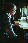 Dick Proenneke reading at desk in his cabin, Upper Twin Lake, Lake Clark National Park, Alaska.