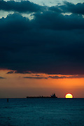 The sun hits the horizon with a tanker ship in the distance.