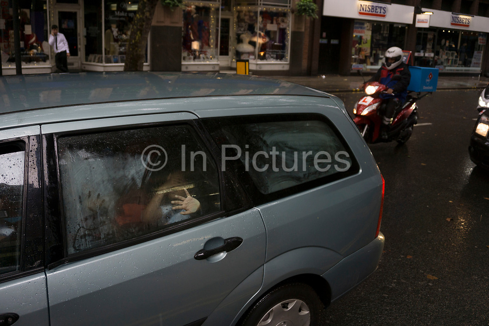 London, UK. Sunday 23rd August 2015. Heavy summer rain showers in the West End. People brave the wet weather armed with umbrellas and waterproof clothing. Steamed up car windows.