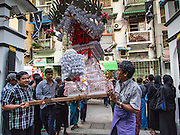 03 NOVEMBER 2014 - YANGON, MYANMAR: Shia Muslims in Yangon carry a coffin representing Hussein bin Ali's coffin into Mogul Mosque (Masjid) during the celebration of Ashura. Shia Muslims in Yangon started the celebration of Ashura Monday. Ashura commemorates the death of Hussein ibn Ali, the grandson of the Prophet Muhammed, in the 7th century. Hussein ibn Ali is considered by Shia Muslims to be the third Imam and the rightful successor of Muhammed. He was killed at the Battle of Karbala in 610 CE on the 10th day of Muharram, the first month of the Islamic calendar. According to Myanmar government statistics, only about 4% of Myanmar is Muslim. Many Muslims have fled Myanmar in recent years because of violence directed against Burmese Muslims by Buddhist nationalists.    PHOTO BY JACK KURTZ