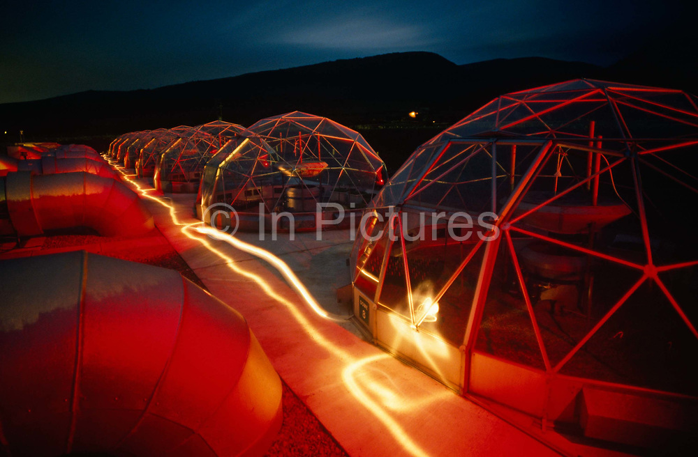 On a dark evening in the Welsh countryside eight ventilated hemispherical glasshouses called Solardomes have been 'painted' with gels and with coloured flash strobes while a torch has streaked whiter light in this scientific facility. Replicating climate change and its effects on plant-life, this experiment run by the University of Aberystwyth has run for 20 years, its research being invaluable to our understanding how rising levels of greenhouse gases (CO2) will affect photosynthesis and therefore plant food growth. By increasing the levels of such gasseous pollutants are we now more sure of how the biology in seminatural grasslands alters. Glowing red, the Solardomes sit like futuristic houses on another planet. Surrounding hills are dark on this evening but there is still detail in the fast-fading sky.