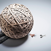 A male model being weighted down by a huge ball made up of elastic bands, with the man reaching for a pair of scissors to be able to free himself.