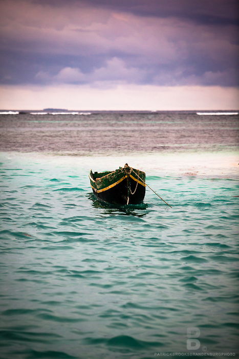 A colorful old traditional canoe used by the Kuna people of the San Blas Islands in the Caribbean Sea during sunset.