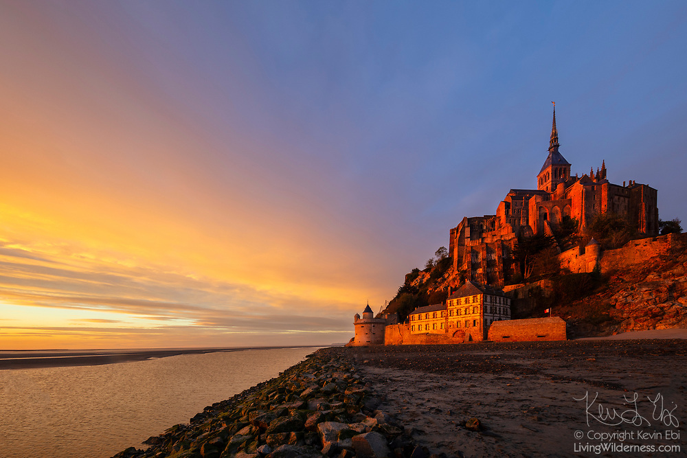 "The golden light of sunset colors the walls of Mont Saint-Michel, a former monastery on a tidal island in Normandy, France. Mont Saint-Michel was known as Mont-Tombe until the 8th century when St. Aubert built a church there after having a vision of the archangel St. Michael. It soon became a pilgrimage center and a Benedictine abbey was built there in 966. After it was partially burned in 1203 during a takeover attempt by King Philip II of France, a monastery, known as La Merveille (""The Wonder""), was built and later fortified. The Mont Saint-Michel monastery was dissolved during the French Revolution (1787–99) and became a prison under Napoleon's reign before the site was restored as a historic monument in 1874. Mont Saint-Michel was designated a UNESCO World Heritage site in 1979. Mont Saint-Michel lies at the mouth of the Couesnon River, which is visible at on the left side of the image. Mont Saint-Michel is cut off from the mainland by sea water during very high tides."