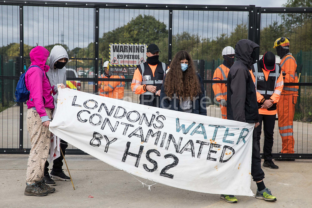 Environmental activists from HS2 Rebellion stand with a banner in front of a gate providing access to a site for the HS2 high-speed rail link on 12 September 2020 in Harefield, United Kingdom. Anti-HS2 activists continue to try to prevent or delay works on the controversial £106bn HS2 high-speed rail link in the Colne Valley where thousands of trees have already been felled.