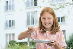 Portrait of young girl eating cake, Bavaria, Germany