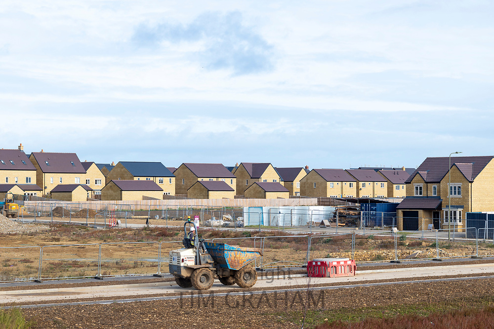 Builder working with dumper truck on a new housing development at West Witney on the outskirts of Oxford, West Oxfordshire, England due to population growth