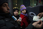 Syrian - Turkish border in Kilis, newly arrived refugees from Aleppo in a bus to Gaziantep. R Mona 9 years, L Fatima 10 years. Because Turkey is saturated with refugees, they will likely get no  help, no work, and no place in a refugee camp. Many refugees return to Aleppo after a few month in Turkey, a country that is now saturated with refugees.