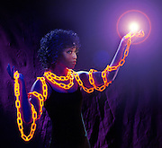 Young black woman wrapped with a glowing chain, hold a light sphere.Black light