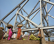 It is morning in Kolkata (Calcutta), West Bengal, India and on the West bank of the Hooghly River the food market is busy with merchandise being brought across the Howrah Bridge. We see coconuts piled on the ground and women carrying sacks on their heads while others stand around them awaiting trade. Above them is the huge British engineering of the bridge which stretches across the water towards the city beyond. The bridge is one of three on the Hooghly River and is a famous symbol of Kolkata and West Bengal. Bearing the daily weight of approximately 150,000 vehicles and 4,000,000 pedestrians. It is one of the longest bridges of its type in the world. The Hooghly River is an approximately 260 km long distributary of the Ganges River and this bridge is one of the finest cantilever bridges in the world.