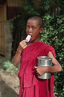 Mandalay, Myanmar --- A young Buddhist monk enjoys an ice cream pop as he goes about his day. Mandalay, Myanmar. --- Image by © Owen Franken/CORBIS