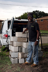 29 August 2007. Lower 9th Ward, New Orleans, Louisiana. <br /> Second anniversary of Hurricane Katrina. Signs of hope and rebuilding. Darryl Ratcliff unloads cinder blocks from his van in the Lower 9th Ward. Daryl is helping an elderly couple to rebuild their home which was washed away when the industrial canal levee breached. Many residents are struggling to return to the still derelict and decimated Lower 9th Ward.<br /> Photo credit; Charlie Varley.