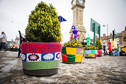 © Licensed to London News Pictures. 27/04/2016. Thirsk UK. Picture shows  flower pots that have been Yarn Bombed in Thirsk. Under the cover of Darkness 300 Yarn bombing street artist's have covered the Town centre of Thirsk, the group has covered bollards, flower pots, the bus stop, tree's, benches, even the local police station. The knitted creations took over 750 balls of wool & have been placed along the route of the Tour De Yorkshire which will pass through the town during it's final stage from Middlesborough to Scarborough on Sunday.  Photo credit: Andrew McCaren/LNP