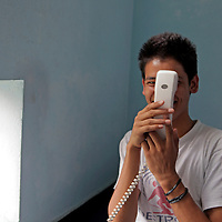 Asia, Nepal, Kathmandu. A young teen embarrased making a phone call.