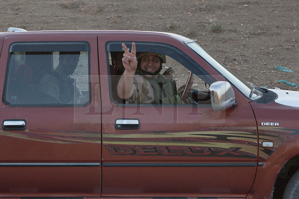 20/10/2016. Bashiqa, Iraq. A Kurdish peshmerga fighter flashes a V for victory sign as he and his colleagues drive forward to take start part of an offensive to retake Mosul from Islamic State militants today (20/10/2016).<br /> <br /> Launched in the early hours of today with support from coalition special forces and air strikes, the attack is part of the larger operation to retake Mosul from the Islamic State, and involves both the Kurds and the Iraqi Army. The city of Bashiqa, around 9 miles north of Mosul, is one of several gateway areas that must be taken before any attempted offensive on Mosul itself.<br /> <br /> Despite the peshmerga suffering several casualties after militants fought back using mortars, heavy machine guns and snipers, the Kurdish forces were quickly taking ground with Haider al-Abadi, the Iraqi prime minister, stating that the operation to retake Mosul was progressing faster than expected. Photo credit: Matt Cetti-Roberts/LNP