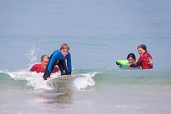 Holidaymakers learning to surf at Fistral Beach in Newquay, Cornwall.
