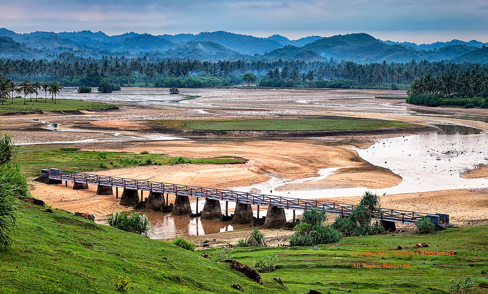 Bridge at Segar Beach: This elevated view is of a nearly dried river bed as it slowly winds under a walking bridge, next to adjacent tropical forests and mist covered hills, Segar beach - Kuta Lombok Indonesia.