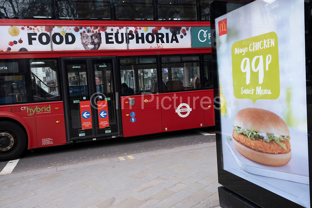Food euphoria advertisement on a passing bus beside a picture of fast food burger for McDonalds on 5th March 2021 in London, England, United Kingdom.