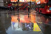 With the reflections of bright advertising behind them, Londoners dash through Piccadiily Circus during a downpour, on 3rd December 2018, in London, UK