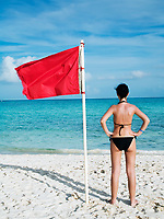 woman standing on te beach near a red flag on the sea meaning that swimming is dangerous and prohibited