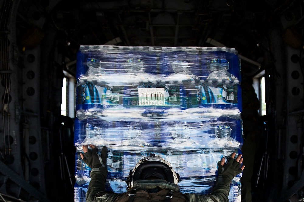 U.S. Navy Chief Naval Aircrewman Helicopter Phillip Freer, assigned to the HM-14, Naval Station Norfolk, Va, pushes a pallet of water onto an MH-53E Sea Dragon helicopter for Hurricane Harvey relief support at Katy, Texas, Aug. 31, 2017. Hurricane Harvey formed in the Gulf of Mexico and made landfall in southeastern Texas, bringing record flooding and destruction to the region. U.S. military assets supported FEMA as well as state and local authorities in rescue and relief efforts.<br /><br />(U.S. Air Force photo by Tech. Sgt. Larry E. Reid Jr.)  Please note: Fees charged by the agency are for the agency's services only, and do not, nor are they intended to, convey to the user any ownership of Copyright or License in the material. The agency does not claim any ownership including but not limited to Copyright or License in the attached material. By publishing this material you expressly agree to indemnify and to hold the agency and its directors, shareholders and employees harmless from any loss, claims, damages, demands, expenses (including legal fees), or any causes of action or allegation against the agency arising out of or connected in any way with publication of the material.